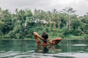 Woman enjoying tropical rain while swimming in infinity pool on Bali