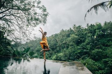 Woman enjoying tropical rain while on infinity pool on Bali