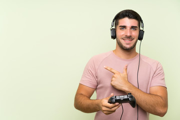 Young handsome man playing with a video game controller over isolated green wall pointing to the...