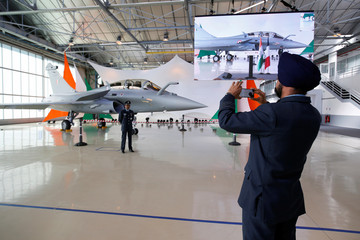 A man takes pictures of the first Rafale fighter jet to the Indian Air Force at the factory of French aircraft manufacturer Dassault Aviation in Merignac near Bordeaux