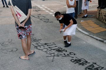 A student holds a spray paint as she protests against the punishment of those students who fight to protect the Lennon walls, one of the symbols of anti-government protest, outside Po Leung Kuk Yao Ling Sun College, in Hong Kong