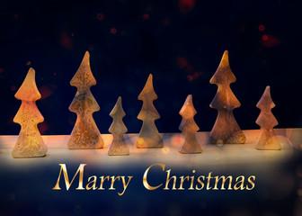 Tannenbäume im Lichtschein bei winterlichem Nachthimmel und mit Text Marry Christmas