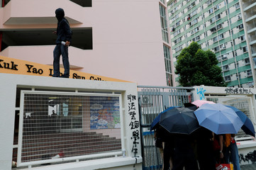 Students try to block the gate outside Po Leung Kuk Yao Ling Sun College, as they protest against the punishment of those students who fight to protect the Lennon walls, one of the symbols of anti-government protest, in Hong Kong