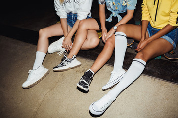 Cropped image of hipster girls sitting on skateboards at night