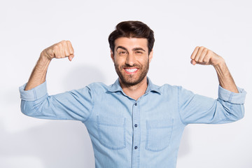 Photo of amazing handsome guy raising arms showing perfect biceps expressing strength wear casual denim shirt isolated white color background