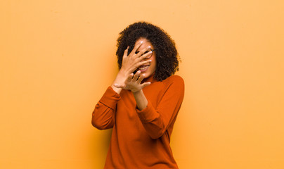young pretty black woman covering face with hand and putting other hand up front to stop camera, refusing photos or pictures against orange wall