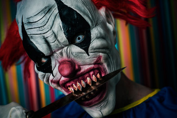 scary evil clown with a knife in his mouth