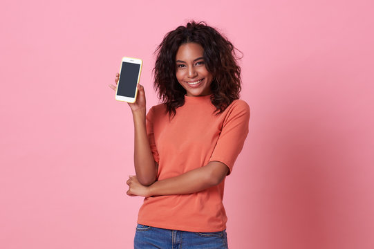 Portrait of happy young african woman showing at blank screen mobile phone isolated over pink background.