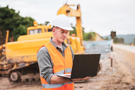 Caucasian young engineer using a laptop on road construction site. Engineer work concept