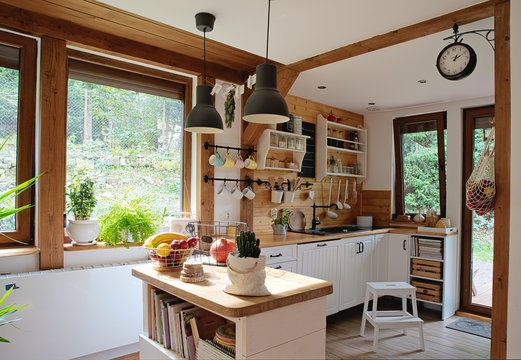 interior of modern kitchen in vintage style with white wooden furniture and rustic detail. Bright indoors with window and wood.