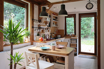 Vintage interior of kitchen in rustic style with wooden furniture and windows. Bright and cozy dining room with decorative detail.