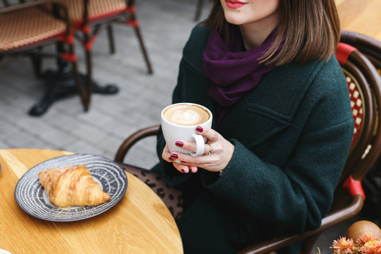 Cup of coffee in women's hands. Young girl wearing green coat sitting at a table in cozy street outdoor cafe and drinking coffee with a croissant. Restaurant terrace in the French style. No face.