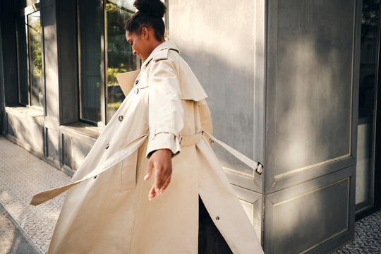 Back view of attractive casual African American girl in stylish trench coat dreamily whirling on street