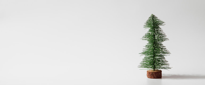 Web Banner Miniature christmas tree on white background with copy space for text. Winter holiday celebration concept.