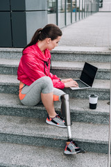 disabled sportswoman using laptop with blank screen while sitting on stairs on street