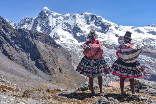 Quechua girls admire Andean mountain views on the Ausungate trail. Cusco, Peru