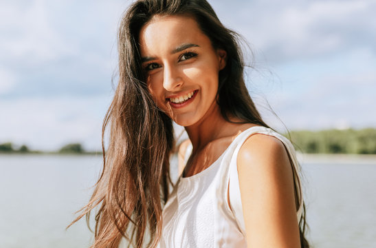 Close-up outdoor portrait of beautiful happy young woman smiling broadly with toothy smile with a windy blowing long hair in the park, posing on nature background.