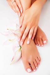 Fotorolgordijn Pedicure manicure pedicure with flower lily close up isolated on white perfect shape hands spa salon