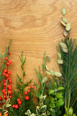 Vertical flat lay of colorful evergreen leaves and bright berries on a polished oak wood background, with copy space