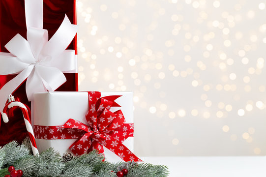 Christmas white and red gift boxes with red ribbon by some snowy fir or pine branches with cones and red berries over a bright light background with natural bokeh and copy space.
