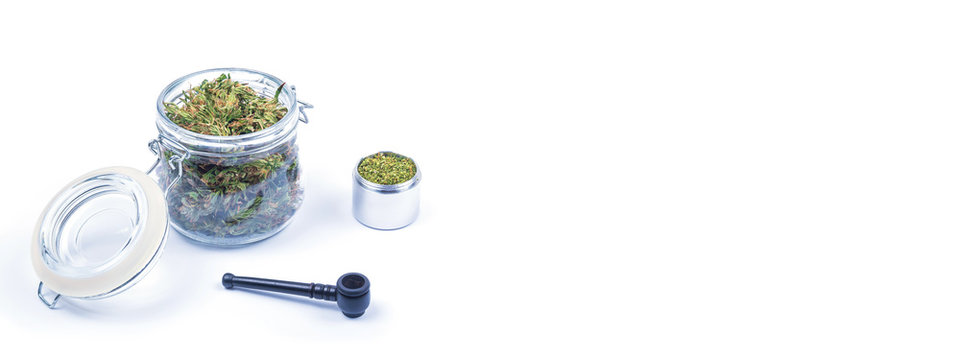 Fresh green buds or flowers of cannabis marijuana in opened transparent glass jar and grinded weed in open aluminum round metal box and smoking pipe on white background. Copy space. Banner.