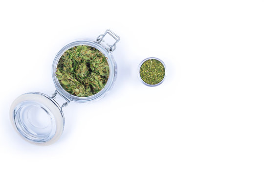 Fresh green buds or flowers of cannabis marijuana weed in an opened glass jar isolated on white background. Alternative treatment. Medical cannabis. Space for text.