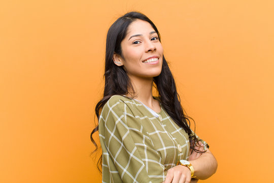 young pretty hispanic woman smiling to camera with crossed arms and a happy, confident, satisfied expression, lateral view against brown wall