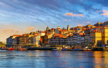 Fototapete - Antique town Porto, Portugal. Sunset sun over silhouettes skyline of roofs of houses along river.