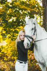 Young attractive blond woman hugs a white horse in a autumn forest.