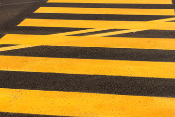 Yellow and black stripes on the street. texture background