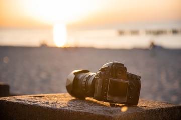 professional dslr camera on the sand on the beach. Dust proof