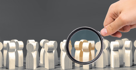 A magnifying glass looks at a crowd of wooden figures of people. society, demographic. group of citizens, rally, political movement or electorate. Customers and buyers, preferences of Population.