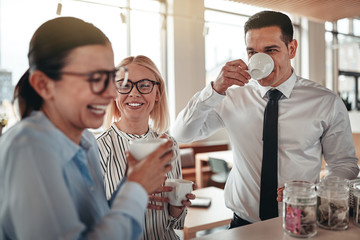 Young businesspeople laughing together during their office coffe