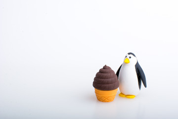 Penguin and ice cream rubber toys, cute animal shaped rubber doll isolated in white background.