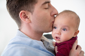 Loving Father Giving 9 Month Old Baby Son A Kiss