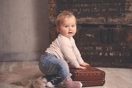 Süßes Baby 1 Jahr sitzt auf altem kleinen Koffer Hintergrund alte Kisten Var. 1