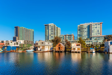 Houseboats on Mission Creek Channel in Mission Bay district in San Francisco, California, USA. Newly developed apartment flats in the background.a