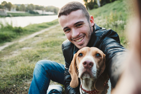 Young man takes a selfie with beloved dog at the park at sunset - Millennial in a moment of relaxation with his four-legged friend