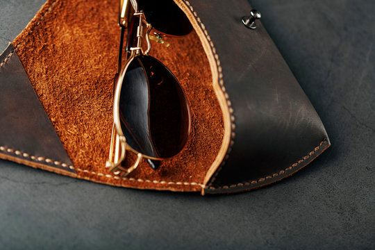 Genuine brown leather glasses case, handmade on a dark background. Glasses inside the case