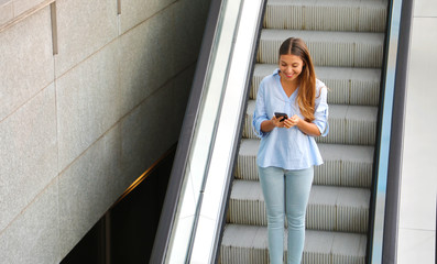 Young business woman messaging with smart phone while descents with the escalator.