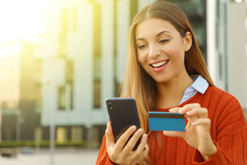 Happy smiling woman wearing sweater paying online holding with smart phone and credit card outdoors in autumn season. Copy space.