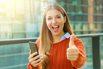 Young beautiful business woman holding smart phone showing thumb up on city street.
