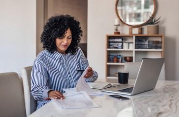 Smiling female entrepreneur going through paperwork at her dining table