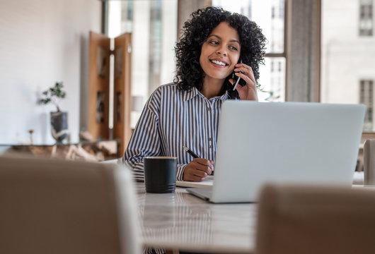 Smiling female entrepreneur sitting at home talking on her cellphone