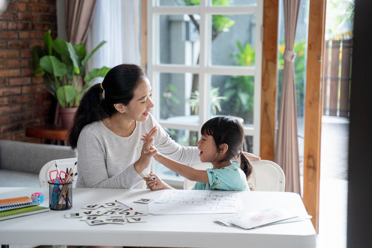 mother and daughter high five during learing to read and write together at home