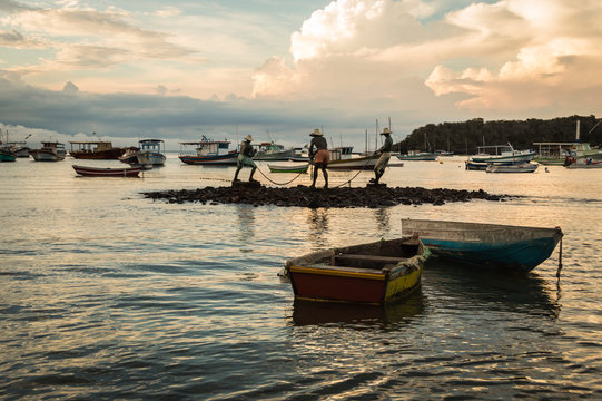 Horizontal view of Three fishermen (Tres pescadores) sculpture and boats at Buzios beach, Brazil during dusk on a cloudy summer day. Beach became famous after being visited by Brigitte Bardot