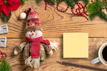 Snowman rag doll and notepad on wooden background