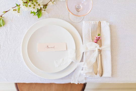 Dishes and cutlery, boho wedding table setting. Wedding card in white plate
