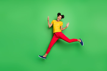 Full length photo of pretty dark skin lady jumping high sports competition jogging participant wear casual yellow t-shirt red pants isolated green background Wall mural