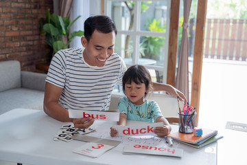 portrait of father teaching toddler how to read by using simple word and letter on a flash card at home